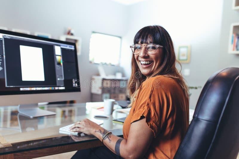Иллюстратор работая на компьютере в офисе стоковые изображения
