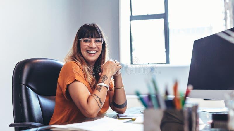 Иллюстратор сидя на ее столе в офисе стоковая фотография