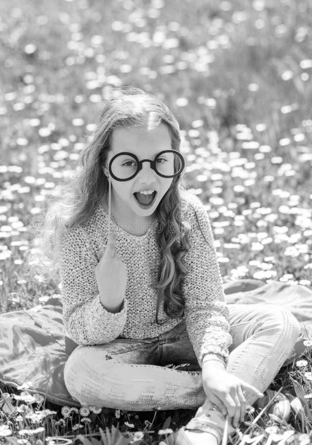 Имейте славный день Девушка сидит на траве на grassplot, зеленой предпосылке Ребенок представляя с eyeglasses картона для фото стоковое фото