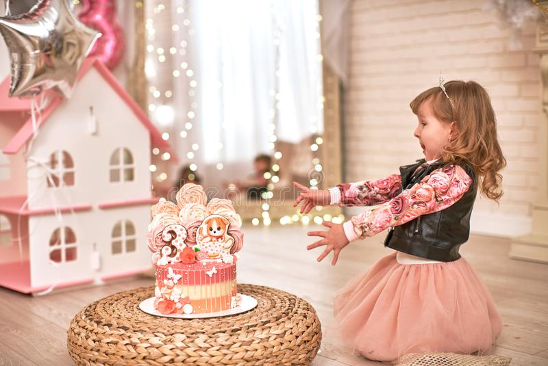 Именниный пирог на 3 лет украшенный с бабочками, котенком пряника с замороженностью и 3 меренга бледная - розовый внутри стоковые фото