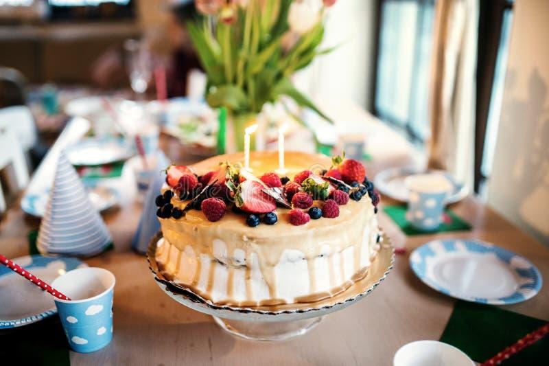 Именниный пирог на стеклянной стойке и ваза с тюльпанами на таблице стоковые фото