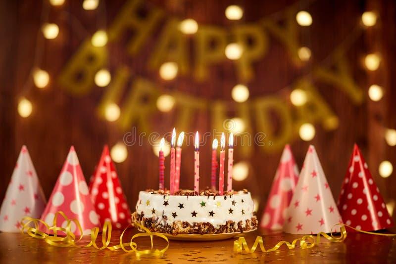 Именниный пирог с днем рождений с свечами на предпосылке гирлянд a стоковые фотографии rf