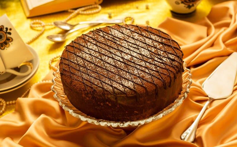Именниный пирог шоколада, чашки, ложки на silk скатерти стоковая фотография