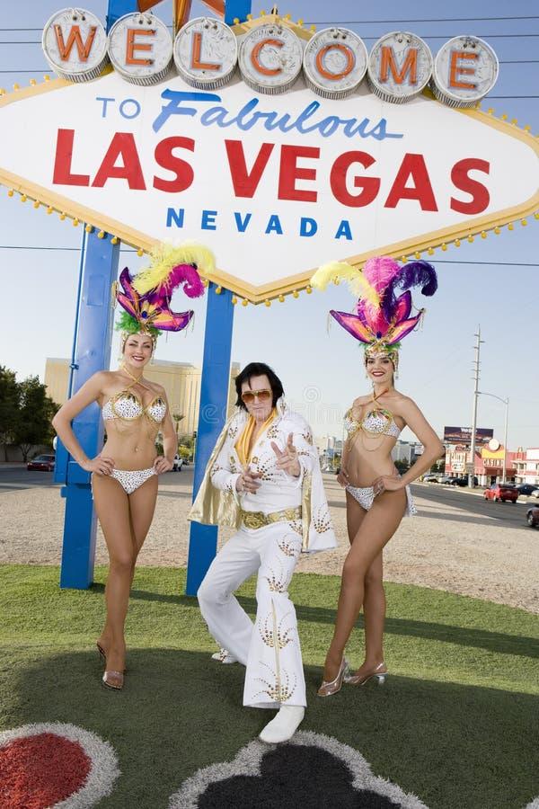 Имитатор Elvis Presley стоя с танцорами казино стоковое изображение rf