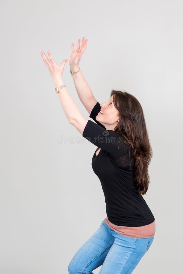 Имитация молодой женщины улавливая что-то из воздуха стоковое фото