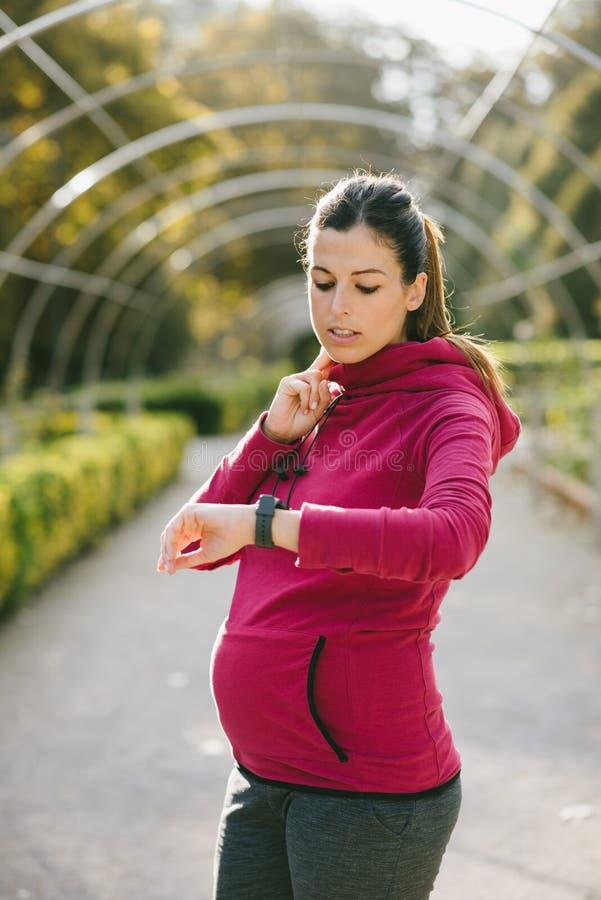ИМП ульс сердца контроля беременной женщины во время тренировки внешней стоковое фото