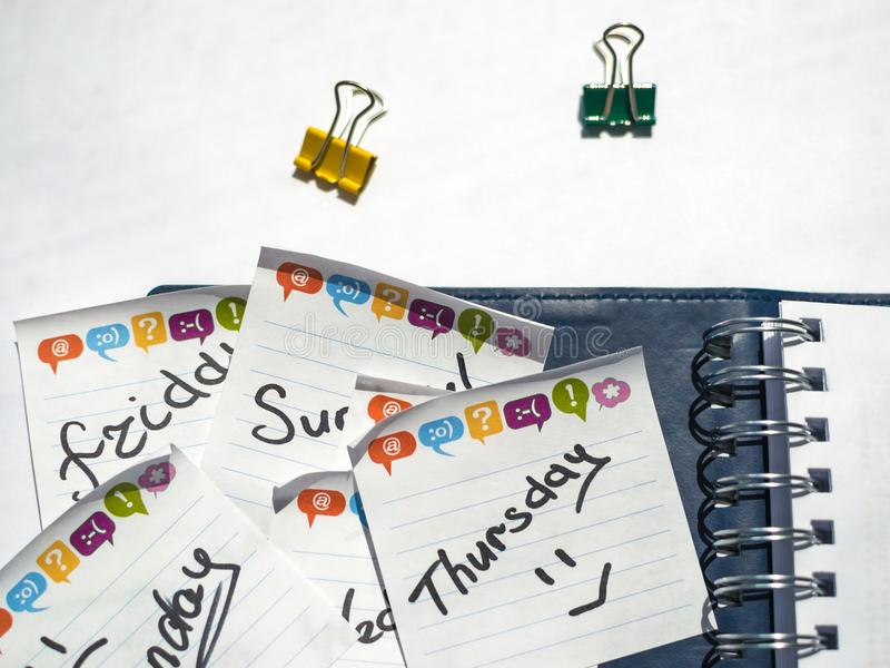 Имя дня недели написанной на липком листе в голубой тетради с веснами стоковая фотография