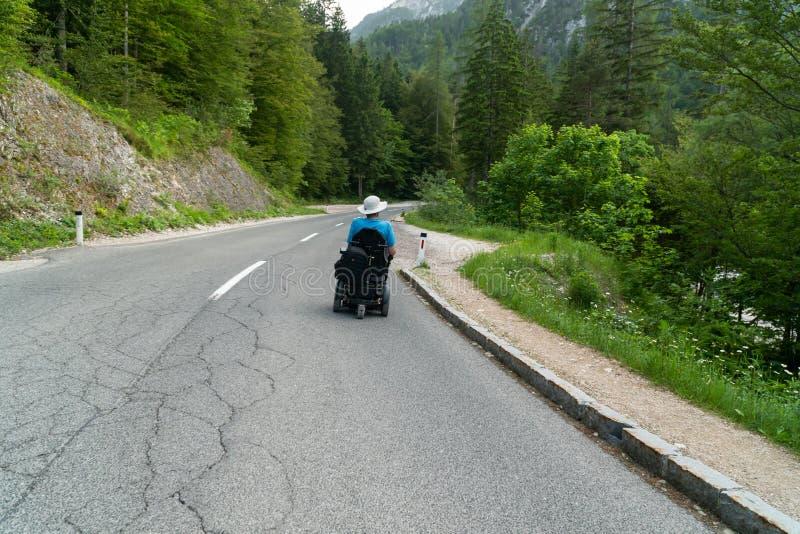 Инвалид в электрической кресло-коляске управляя на улице, дорога стоковые фотографии rf