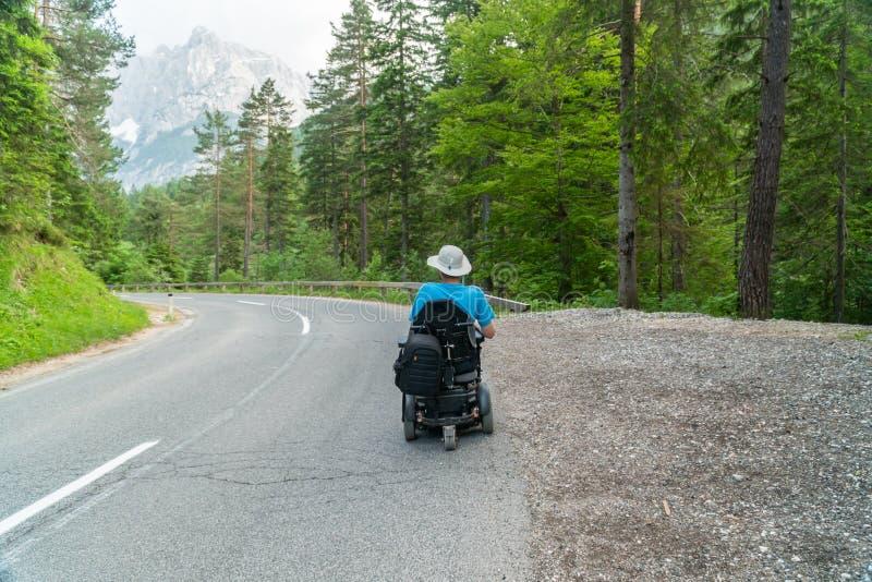 Инвалид в электрической кресло-коляске управляя на улице, дорога стоковое фото rf