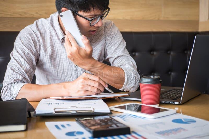 Инвестиционный проект бизнесмена работая на ноутбуке с документом отчета и проанализировать, расчетливые финансовые данные на диа стоковое фото
