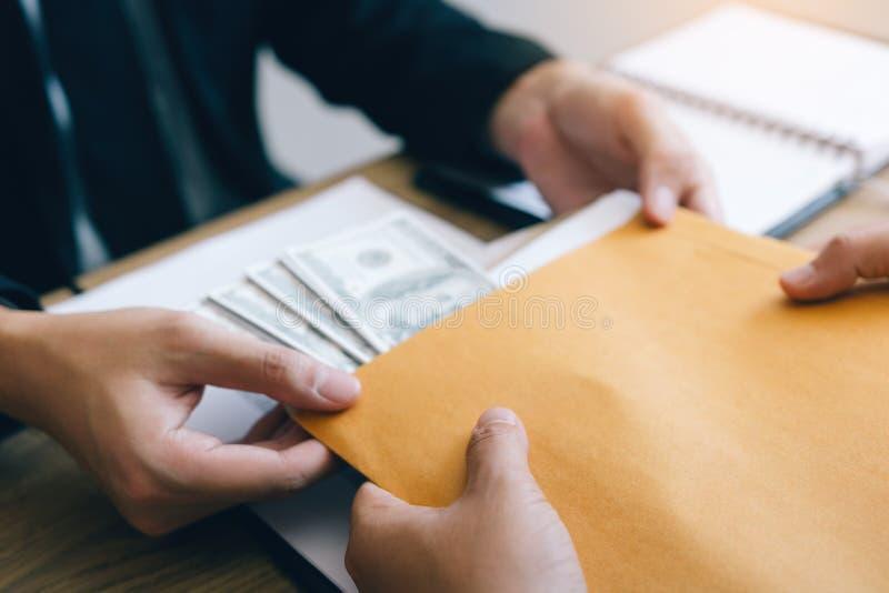 2 инвестора имеют секреты дела с наличными деньгами будучи помещанными в конверте документа для того чтобы подкупить работники стоковое фото
