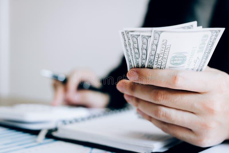Инвесторы высчитывают на стоимостях инвестирования калькулятора и держат примечания наличных денег в руке стоковые изображения