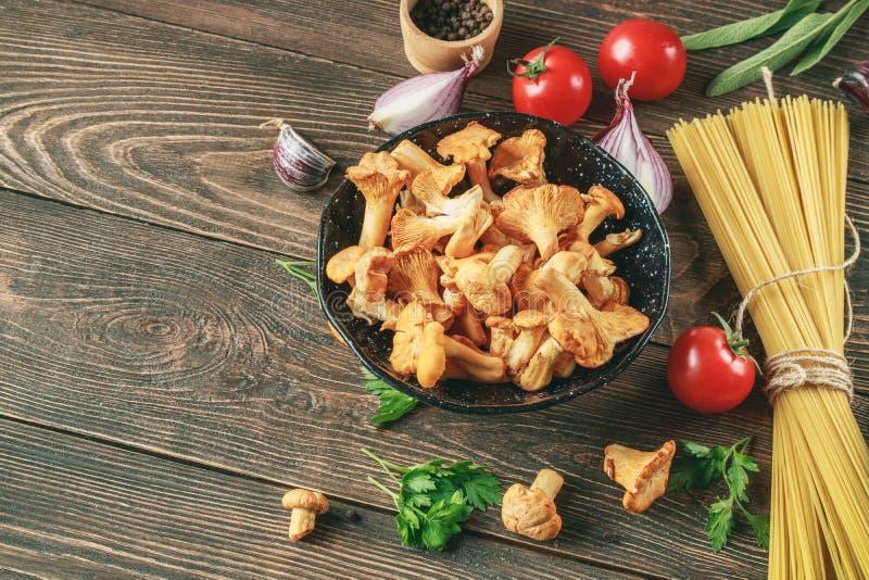 Ингредиенты для варить спагетти с лисичками на деревянной предпосылке стоковое изображение rf