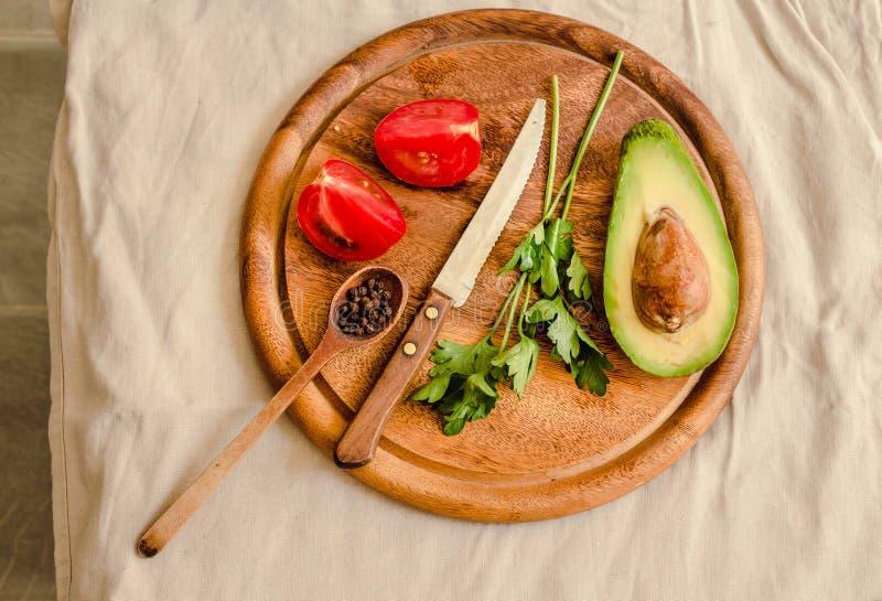 Ингредиенты для гуакамоле на деревянной доске Петрушка, авокадо, томаты, чеснок, черный перец стоковое фото