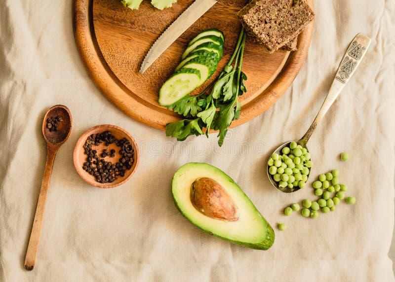Ингредиенты для гуакамоле на деревянной доске Петрушка, авокадо, чеснок, черный перец Взгляд сверху Vegan и вегетарианская концеп стоковые изображения