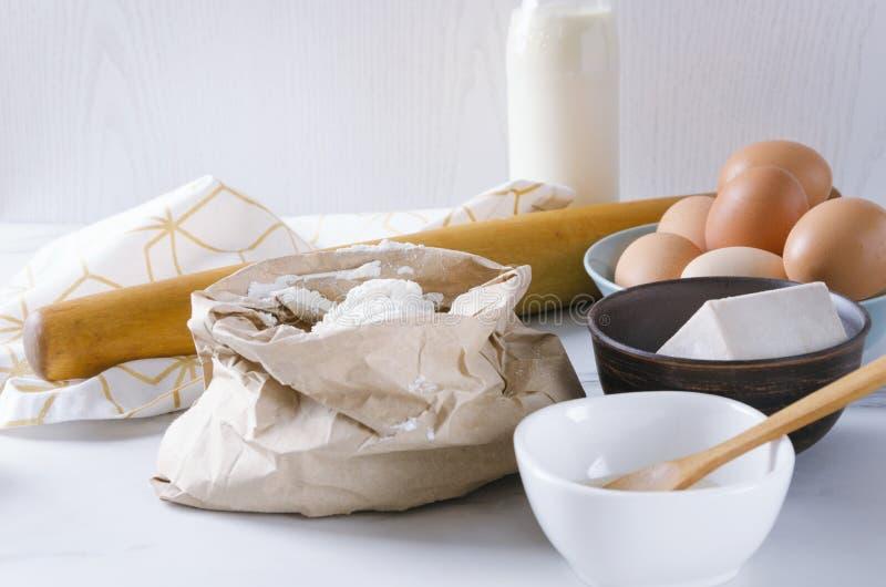Ингредиенты для замешивать тесто Мука в бумажном мешке, яйца, сухие дрожжи, молоко Утвари и компоненты кухни для теста стоковое фото rf
