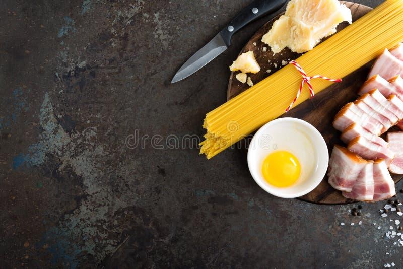 Ингридиенты для варить макаронные изделия Carbonara, спагетти с pancetta, яичко и трудный сыр пармесан томатов спагетти макаронны стоковые фотографии rf