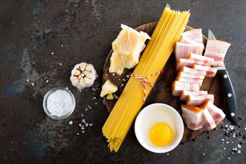 Ингридиенты для варить макаронные изделия Carbonara, спагетти с pancetta, яичко и трудный сыр пармесан томатов спагетти макаронны стоковое изображение rf