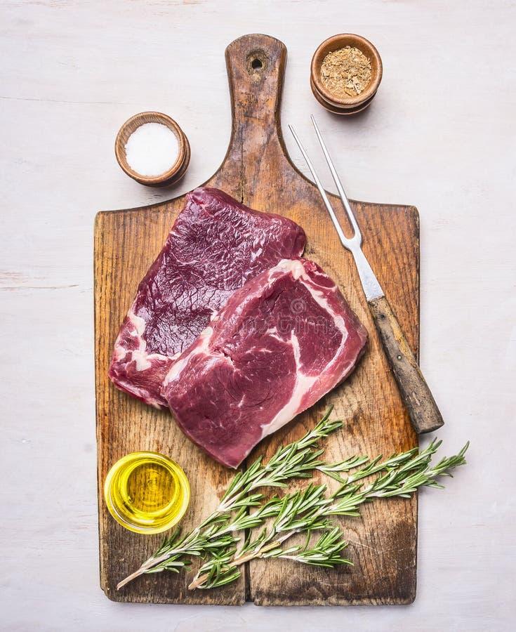 Ингридиенты для варить стейк мяса сырцовый с розмариновым маслом, перцем, специями и маслом на деревенской деревянной предпосылке стоковая фотография rf