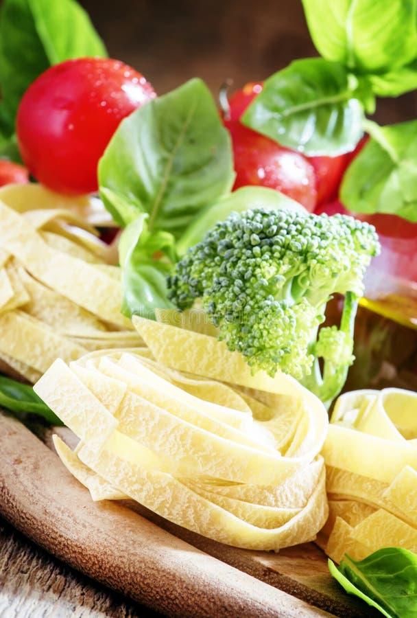 Ингридиенты для варить fettuccine макаронных изделий с брокколи, томатами стоковое фото rf