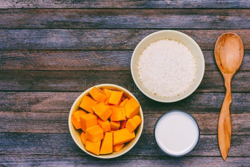 Ингридиенты для делать кашу тыквы хлопья риса, молоко, куски тыквы и деревянная ложка на предпосылке деревянного grunge ретро стоковая фотография rf