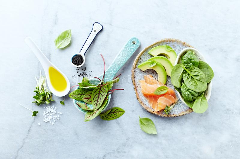 Ингридиенты для здорового салата на серой каменной предпосылке Копченая семга, авокадо, шпинат, щавель, radis пускает ростии, чер стоковое изображение