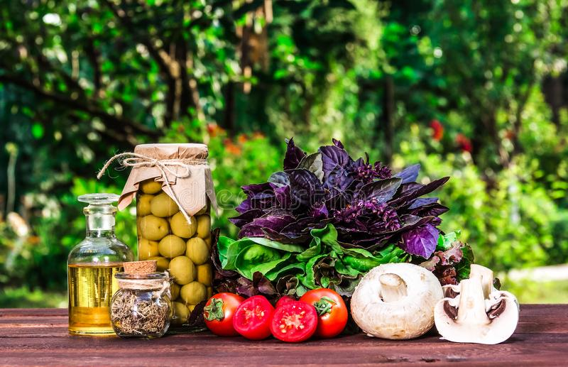 Ингридиенты для салата лета Оливки, базилик, томаты, грибы и оливковое масло на таблице стоковое изображение