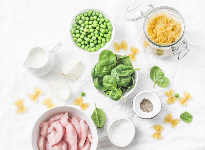 Ингридиенты на варить одно шпинат цыпленка бака сметанообразные и макаронные изделия farfalle зеленых горохов на белой предпосылк стоковое фото