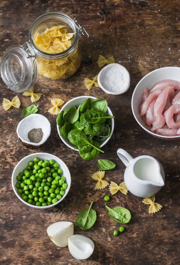 Ингридиенты на варить одно шпинат цыпленка бака сметанообразные и макаронные изделия farfalle зеленых горохов на деревянной предп стоковое фото