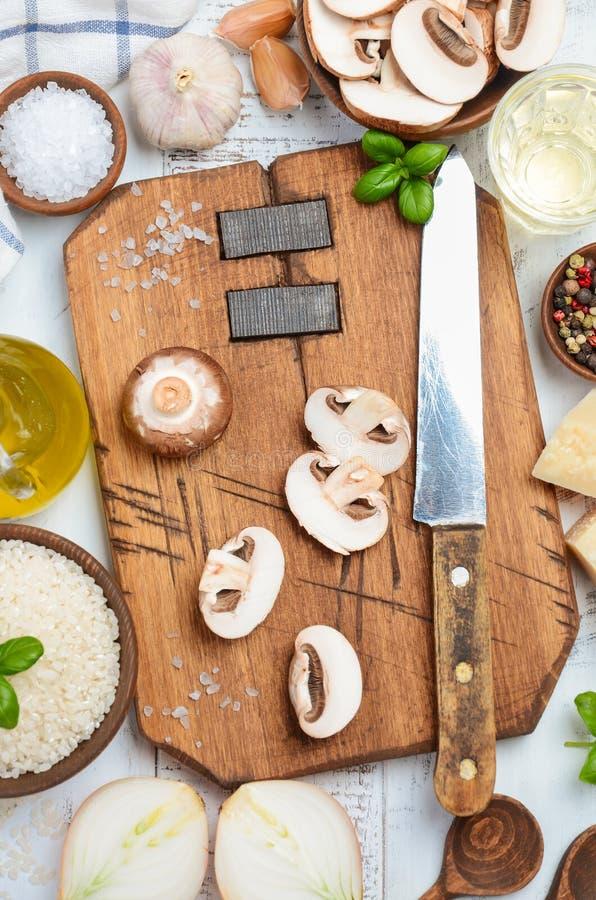 Ингридиенты ризотто - рис, сыр, чеснок, грибы, масло, лук, белая деревянная предпосылка стоковое изображение