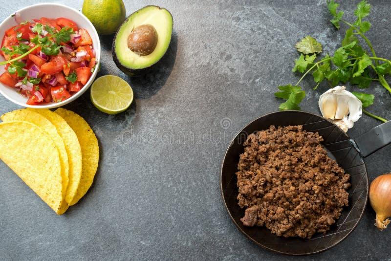 Ингридиенты тако с зажаренными в духовке говядиной, сальсой tomatoe, авокадоом и h стоковое фото