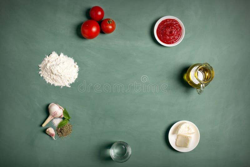 Ингридиенты пиццы на зеленой доске стоковые фото