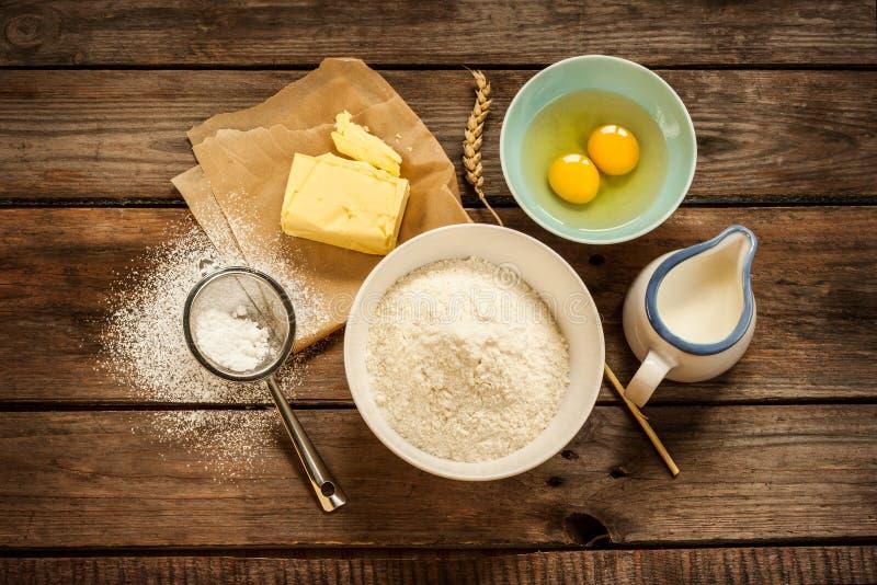Ингридиенты рецепта теста на винтажном сельском деревянном кухонном столе стоковое изображение