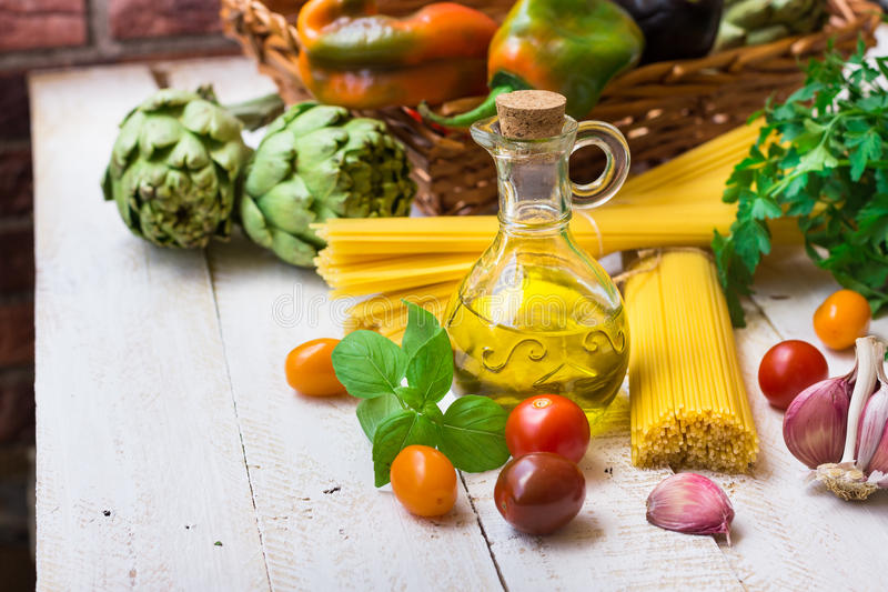 Ингридиенты для варить итальянский обедающий, оливковое масло в бутылке, спагетти, базилике, чесноке, томатах вишни, петрушке, ов стоковые фотографии rf