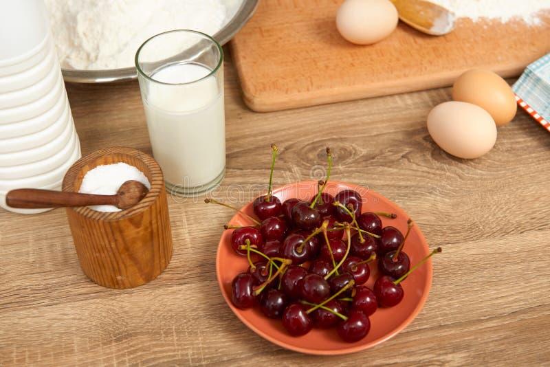 Ингридиенты для печь печений - flour, сломанное яичко, вишня, клубника на деревянной предпосылке Сырцовые утвари еды и кухни здор стоковое фото