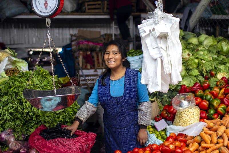 Индигенная молодая женщина усмехаясь и продавая овощи стоковые фотографии rf