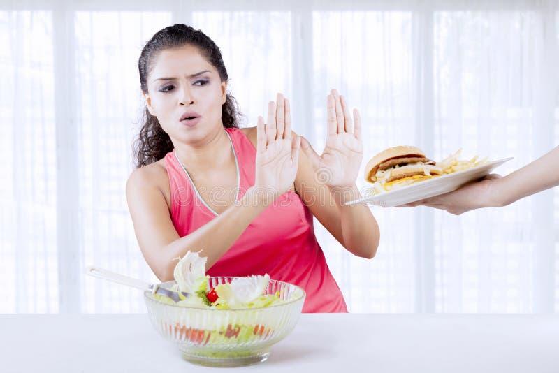 Индийская женщина говоря нет к высококалорийной вредной пище стоковые фотографии rf