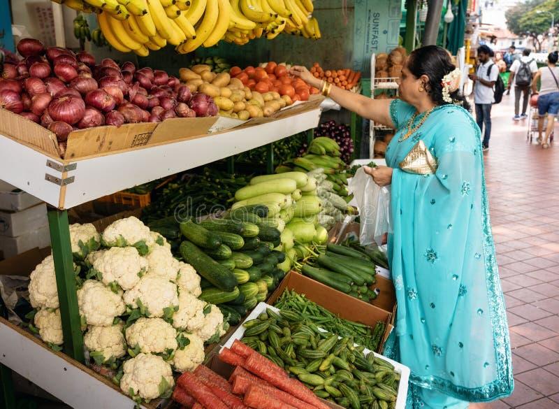 Индийская женщина покупает фрукты и овощи на рынке стоковая фотография