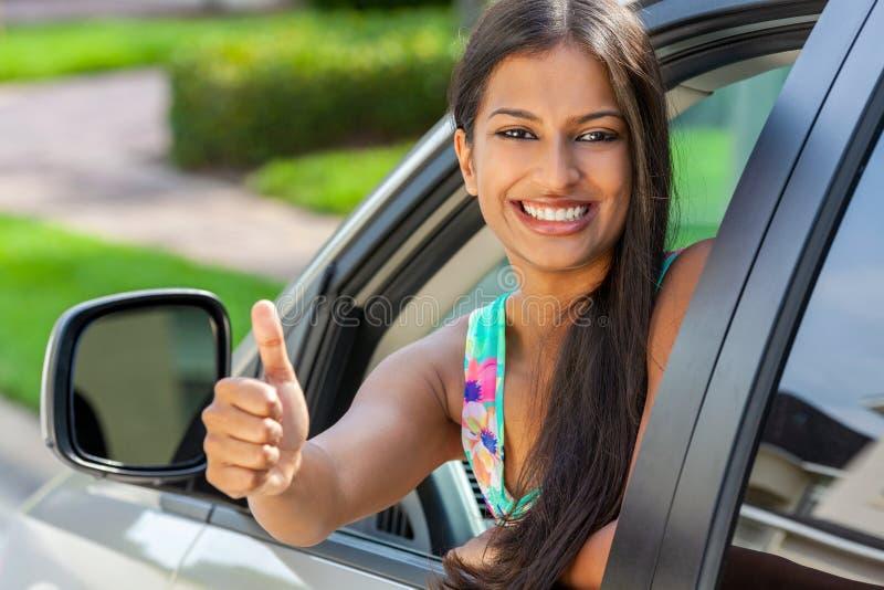 Индийские азиатские большие пальцы руки девушки молодой женщины вверх по управлять усмехаться автомобиля стоковые изображения rf