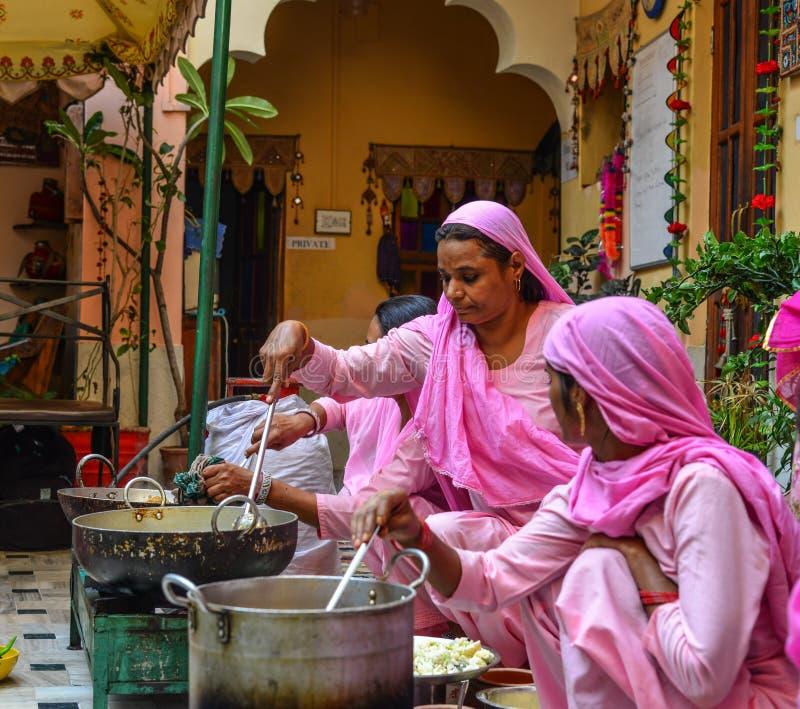Индийские женщины варя традиционную еду стоковое фото rf