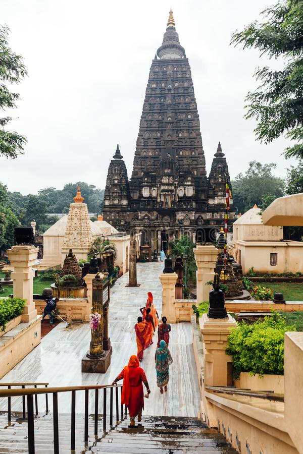 Индийские люди идя на босые ноги к виску Mahabodhi для молят и паломник пока идущ дождь на Bodh Gaya, Бихаре, Индии стоковые фотографии rf