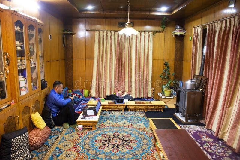 Индийские люди семьи сидя для того чтобы ослабить в живущей комнате гостевого дома на деревне Leh Ladakh в Джамму и Кашмир, Индии стоковое изображение rf
