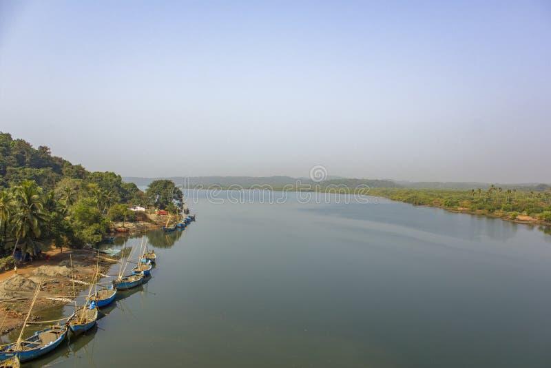 Индийские работники извлекают песок в пути реки, виде с воздуха больших голубых шлюпок на береге и зеленых пальмах стоковые фотографии rf