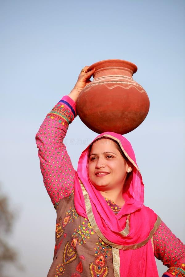 Индийские сельские женщины принимая бак воды на ее главном положении в аграрное поле стоковые изображения