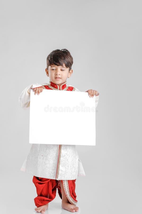Индийский/азиатский мальчик в этнической носке и показывать пустой шильдик стоковые изображения rf