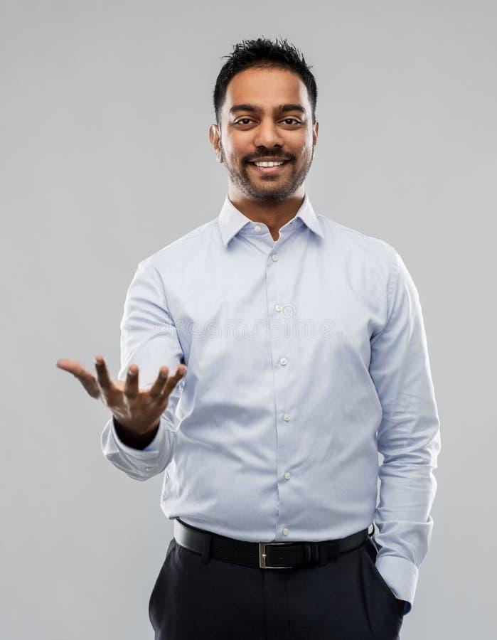 Индийский бизнесмен держа что-то невидимый стоковое фото rf