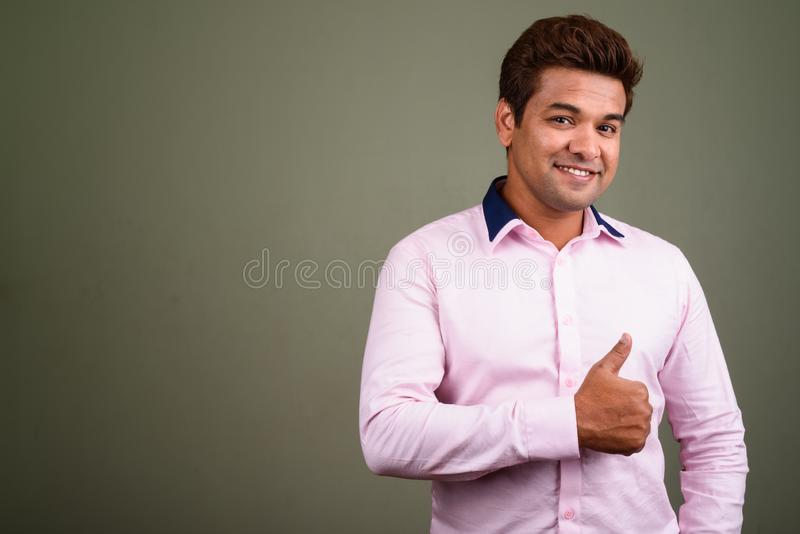 Индийский бизнесмен нося розовую рубашку против покрашенной предпосылки стоковое фото rf