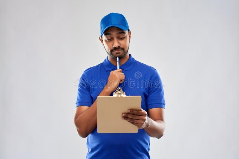 Индийский работник доставляющий покупки на дом с доской сзажимом для бумаги в сини стоковые фото