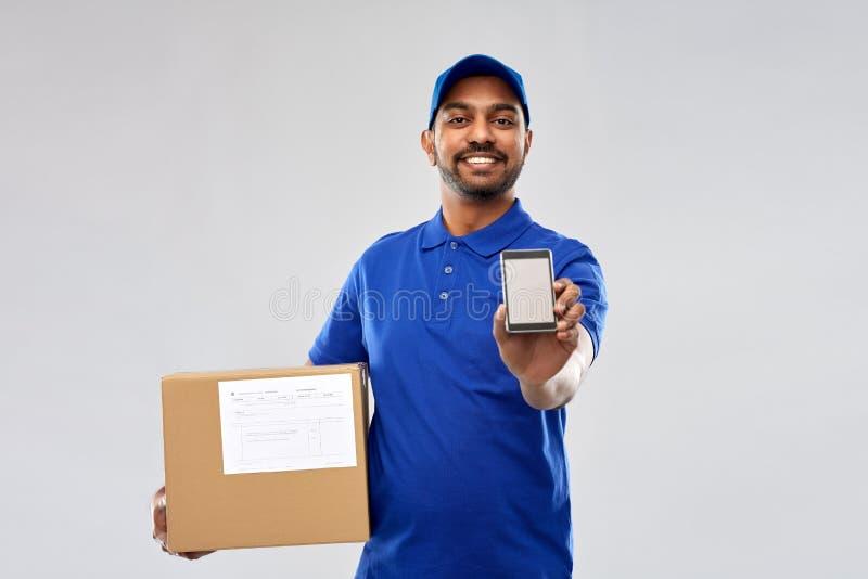 Индийский работник доставляющий покупки на дом с коробкой смартфона и пакета стоковое изображение rf