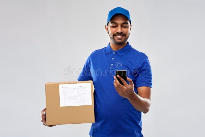 Индийский работник доставляющий покупки на дом с коробкой смартфона и пакета стоковое изображение